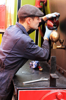 a driver preparing a steam locomotive for operation